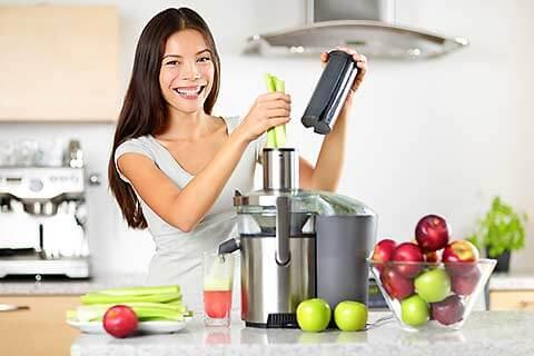 Frau mit Gemüse und Entsafter